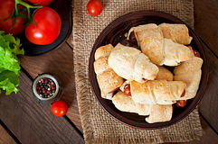 Sausage in the dough sprinkled with sesame seeds Stock Image