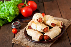 Sausage in the dough sprinkled with sesame seeds Royalty Free Stock Images
