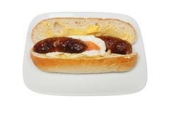 Sausage and egg sandwich. Sausage and fried egg in a sub roll on a plate isolated against white Royalty Free Stock Photo
