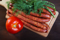 Sausage fennel and a tomato on an  wooden table Stock Image