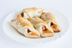 Sausage in flaky pastry. On a white dish Royalty Free Stock Image