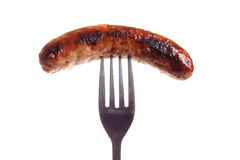 Sausage on a fork. Photograph of a sausage on fork shot in studio on a plain white background Royalty Free Stock Image
