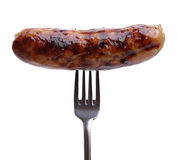 Sausage on a fork. Grilled sausage on a fork against white background Royalty Free Stock Photography