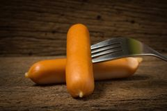 sausage on fork on old wood Stock Images