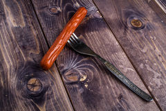 Sausage on fork. Sausage on the wood background Royalty Free Stock Image