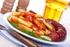 Sausage and french fries Stock Images