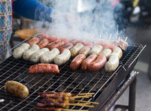 Sausage. Fresh sausage and hot dogs grilling outdoors on a gas barbecue grill Royalty Free Stock Images