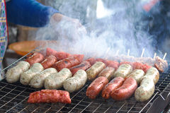Sausage. Fresh sausage and hot dogs grilling outdoors on a gas barbecue grill Stock Photography