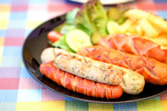 Sausage fried and french fries with vegetables. Stock Image