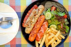 Sausage fried and french fries with vegetables. Royalty Free Stock Photos