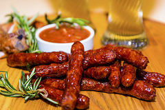 Sausage and fried pork ribs with beer. Delicious sausage and fried pork ribs with beer on a wooden board in the pub Royalty Free Stock Image