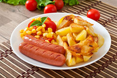 Sausage with fried potatoes and vegetables Stock Photos