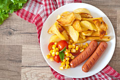 Sausage with fried potatoes and vegetables Stock Images