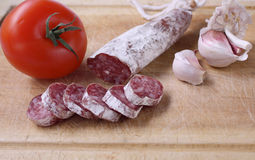 Sausage(fuet). Sausage with tomato and garlic on a wooden board Stock Image