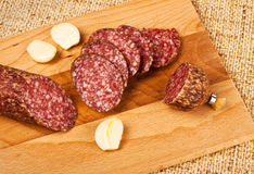 Sausage and garlic on cutting board Royalty Free Stock Photo