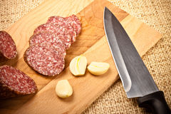 Sausage, garlic and knife Stock Photography