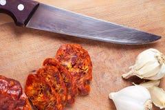 Sausage, garlic and knife Stock Photos