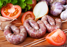 Sausage with garlic and tomatoes. Ingredients for cooking. Food cusine Royalty Free Stock Images