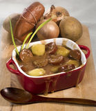 Sausage goulash with potatoes. In a red ceramic rectangular pot with some ingredients in the background and wooden spoon in the foreground Royalty Free Stock Photography