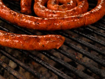 Sausage grill. A tasty sausage on grill, read and oily stock image