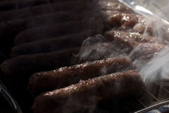 Sausage on grill. Cooking sausage on grill with smoke Royalty Free Stock Photography