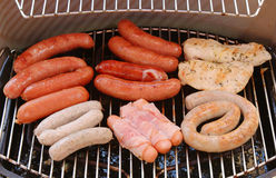 Sausage grill. Sausage, bratwurst bbq grill on grid royalty free stock photo