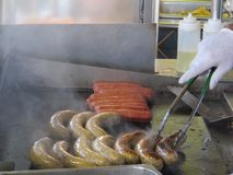 Sausage on the Grill. Sausage and condiments on the grill royalty free stock photo
