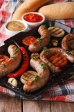 Sausage with grilled vegetables and buns, sauce. Vertical stock photos
