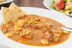 Sausage gumbo soup. A bowl of chicken and sausage gumbo soup with a salad royalty free stock image