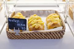 Sausage and ham bun in basket with name and price on black sign Royalty Free Stock Images