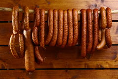 Sausage hanged on wooden background. Many smoked sausage hanged on wooden background Royalty Free Stock Images