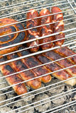 Sausage and hot dogs grilling outdoors Stock Photos
