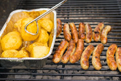 Sausage, hot dogs and potatoes on grill Royalty Free Stock Image