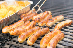 Sausage, hot dogs and potatoes on grill Stock Photos