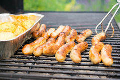 Sausage, hot dogs and potatoes on grill Stock Images