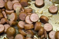 Sausage or kielbasa on grill. Closeup of sliced sausage or kielbasa cooking on a grill stock photography