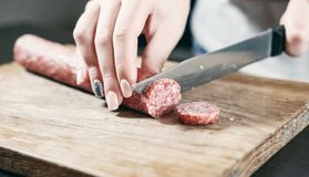Sausage, knife, hands of woman, thick pieces, wooden plank, knife in female hands, woman cuts the sausage stock images