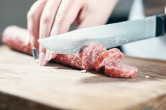 Sausage, knife, hands of woman, thick pieces, wooden plank, knife in female hands, woman cuts the sausage stock photo