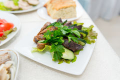 Sausage krovyanka, cut into pieces with fresh cucumber and greens close-up. Royalty Free Stock Image