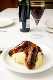 Sausage and mash. A dinner table set with sausage and mash and red wine royalty free stock images