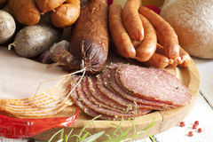 Sausage and meat assortment on cutting board Royalty Free Stock Images