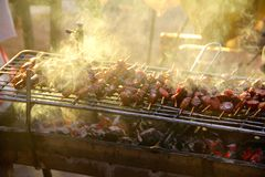 Sausage and meat skewers on the grill in the sun Royalty Free Stock Image