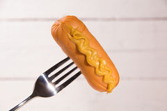 Sausage with mustard on a fork Stock Photography