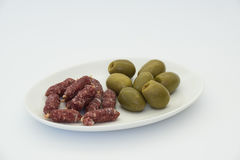 Sausage and olive. On white plate Royalty Free Stock Images