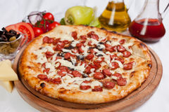 Sausage Pizza. With cheese, oil and tomatoes royalty free stock photography