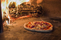 Sausage pizza in a wood oven. Pizza with smoked cheese and sausage in a traditional wood oven Royalty Free Stock Image