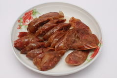 Sausage. A plate of delicious sausages on a white background Royalty Free Stock Photography