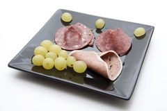 Sausage plate with grapes Stock Photo