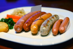 Sausage on a plate. Row of sausage steak on a plate stock image