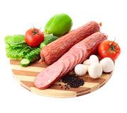 Sausage on plate with vegetables. Isolated on white background Royalty Free Stock Image